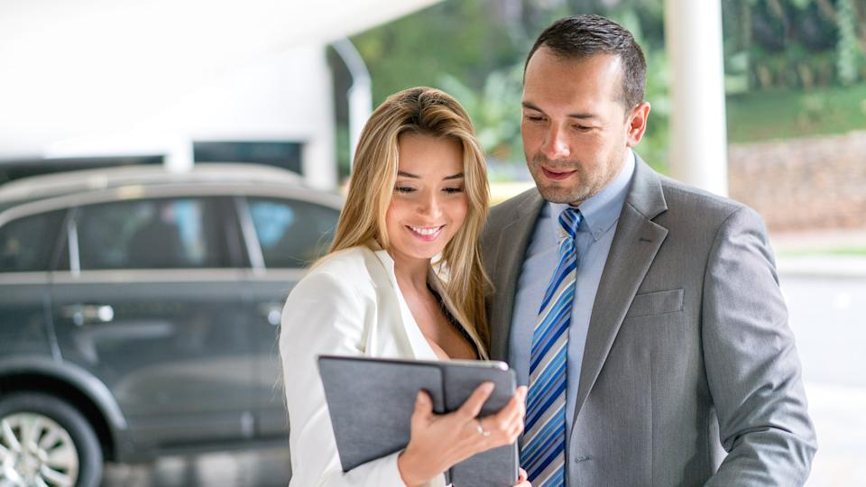 Business couple at the car dealership buying a car and looking at models on a tablet computer.