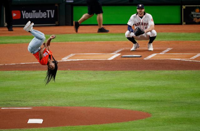 """Gymnast <a class=""""link rapid-noclick-resp"""" href=""""/olympics/rio-2016/a/1112764/"""" data-ylk=""""slk:Simone Biles"""">Simone Biles</a> performs a flip after throwing out the ceremonial first pitch prior to Game 2 of the World Series between the <a class=""""link rapid-noclick-resp"""" href=""""/mlb/teams/houston/"""" data-ylk=""""slk:Houston Astros"""">Houston Astros</a> and the <a class=""""link rapid-noclick-resp"""" href=""""/mlb/teams/washington/"""" data-ylk=""""slk:Washington Nationals"""">Washington Nationals</a> at Minute Maid Park on Wednesday in Houston. (Tim Warner/Getty Images)"""