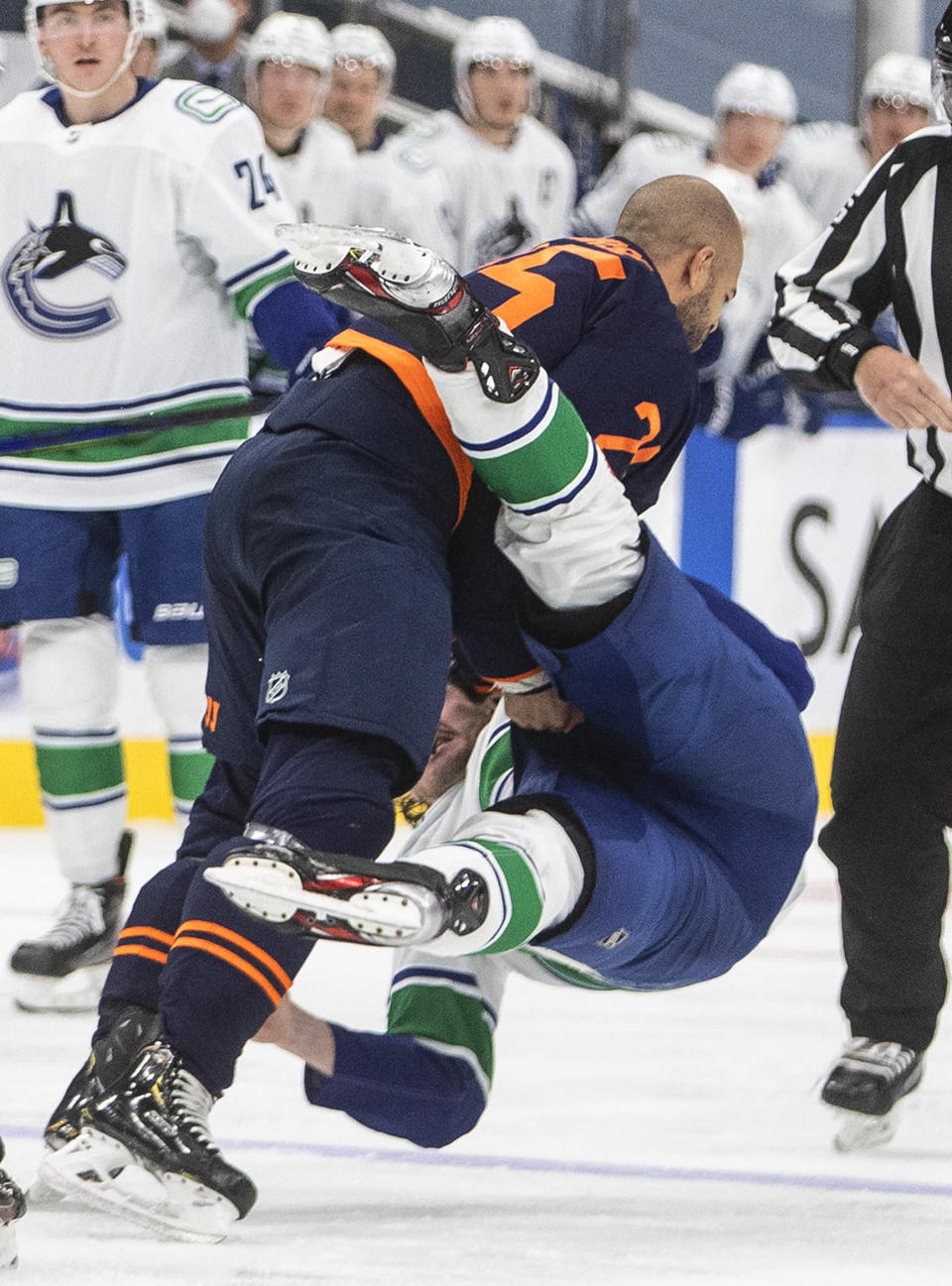 Edmonton Oilers' Darnell Nurse (25) and Vancouver Canucks' Zack MacEwen (71) fight during the third period of an NHL hockey game Thursday, May, 6, 2021, in Edmonton, Alberta. (Jason Franson/The Canadian Press via AP)