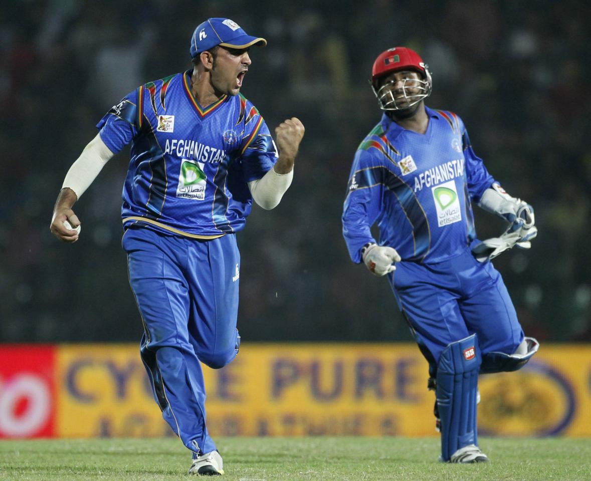 Afghanistan's Samiullah Shenwari (L) and wicketkeeper Mohammad Shahzad celebrate the dismissal of Bangladesh's Nasir Hossain during their Asia Cup 2014 one-day international (ODI) cricket match in Fatullah March 1, 2014. REUTERS/Andrew Biraj (BANGLADESH - Tags: SPORT CRICKET)