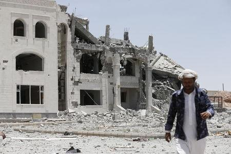 A Houthi militant walks at the yard of residence of the military commander of the Houthi militant group, Abdullah Yahya al Hakim, after an air strike destroyed it, in Sanaa April 28, 2015. REUTERS/Khaled Abdullah