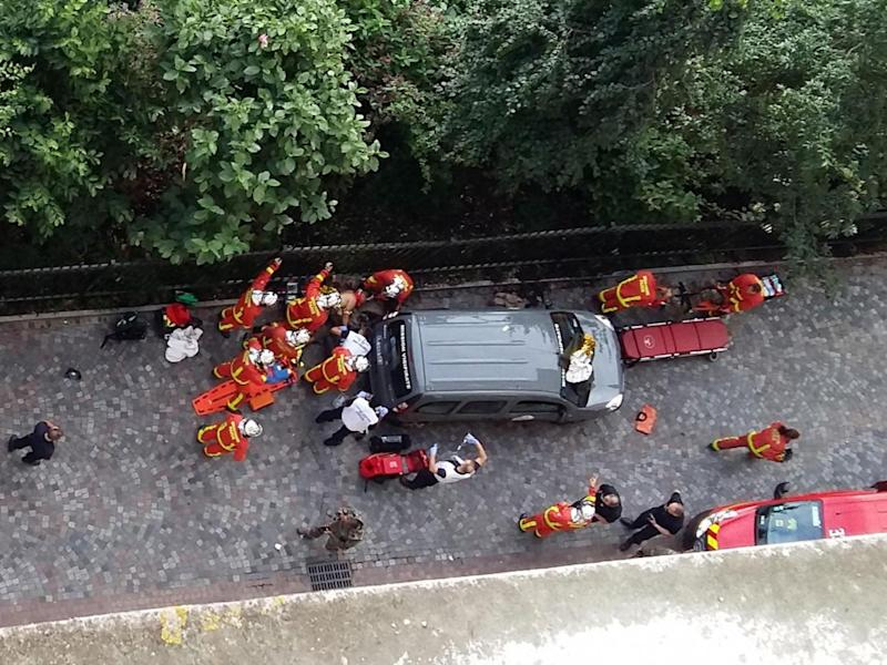 Officials and rescuers gather near vehicles after a car slammed into soldiers on patrol in Levallois-Perret (THIERRY CHAPPE/AFP/Getty Images)