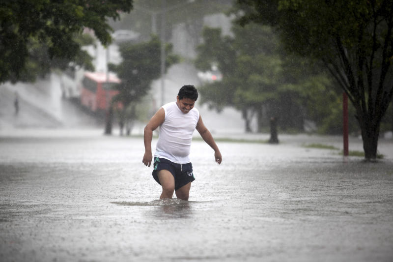 A man walks through a flooded street during heavy rains caused by Tropical Storm Ingrid in the Gulf port city of Veracruz, Mexico, Friday Sept. 13., 2013. Mexican authorities rushed to evacuate neighborhoods located near riverbanks in eight Veracruz townships as Ingrid lashed the coast with heavy rains, threatening more damage in a state where landslides and flooding have killed dozens of people in recent weeks. (AP Photo/Felix Marquez)