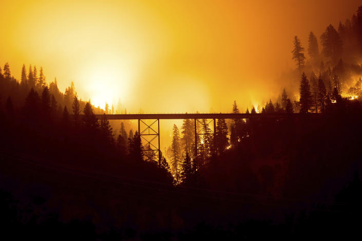 Seen in a long exposure photograph, the Dixie Fire burns behind a bridge in Plumas County, Calif., on Sunday, July 25, 2021. (AP Photo/Noah Berger)