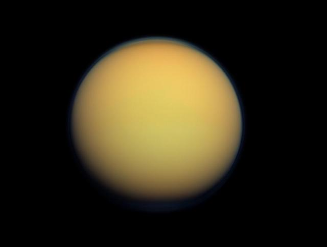 This image provided by NASA shows Saturn's largest moon Titan. A new study being released on Thursday, June 14,2012 suggests the presence of a hydrocarbon lake and several ponds near the equator of Titan, a surprise to scientists who thought lakes only existed at the poles. (AP Photo/NASA)