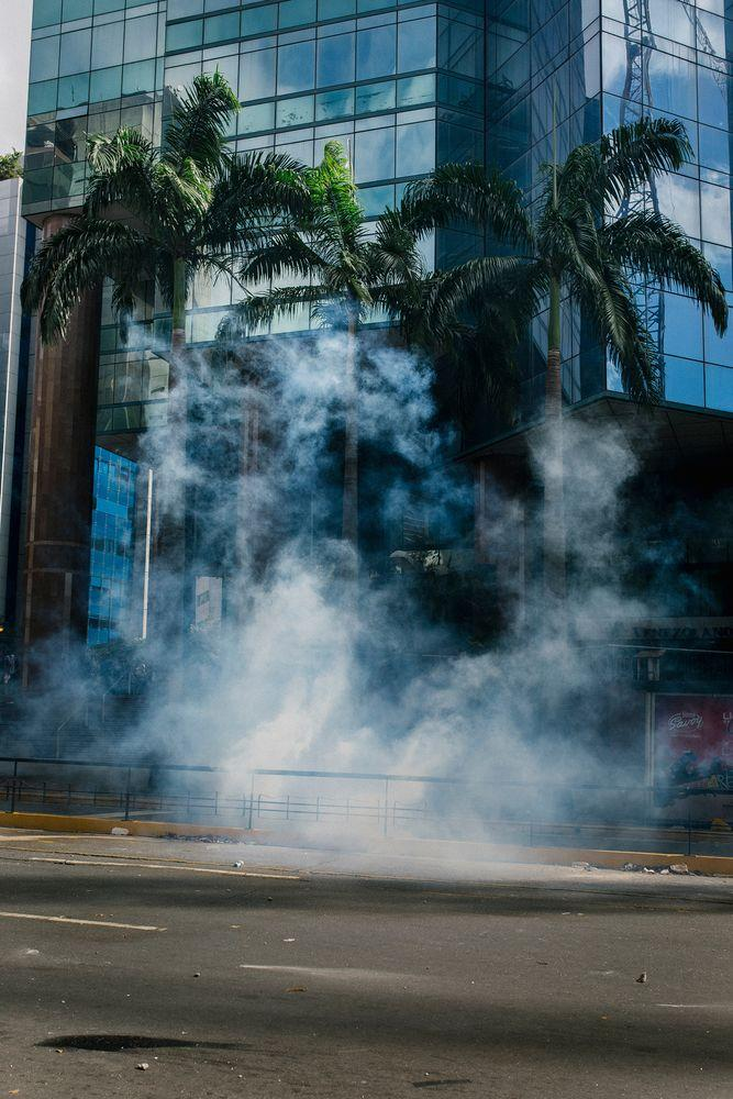 Tear gas floats over the pavement during a protest in El Rosal in Caracas on Jan. 23, 2019.