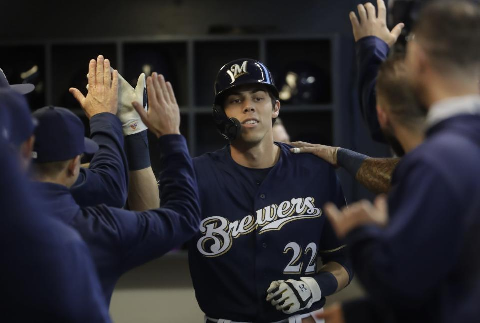 Milwaukee Brewers' Christian Yelich is congratulated after hitting a home run during the first inning of a baseball game against the St. Louis Cardinals Saturday, March 30, 2019, in Milwaukee. (AP Photo/Morry Gash)