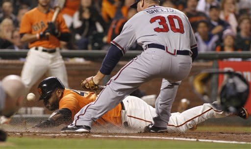 San Francisco Giants' Pablo Sandoval scores Atlanta Braves pitcher Ben Sheets covers home plate during the third inning of a baseball game in San Francisco, Friday, Aug. 24, 2012. (AP Photo/George Nikitin)