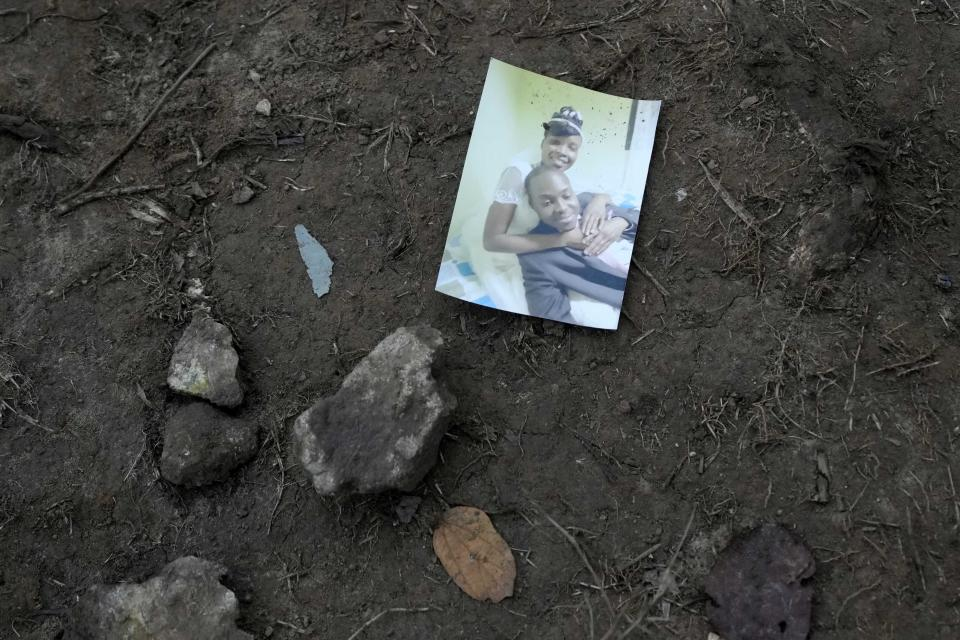 A family snapshot lies on the ground near a trail used by migrants, near Acandi, Colombia, Wednesday, Sept. 15, 2021. (AP Photo/Fernando Vergara)
