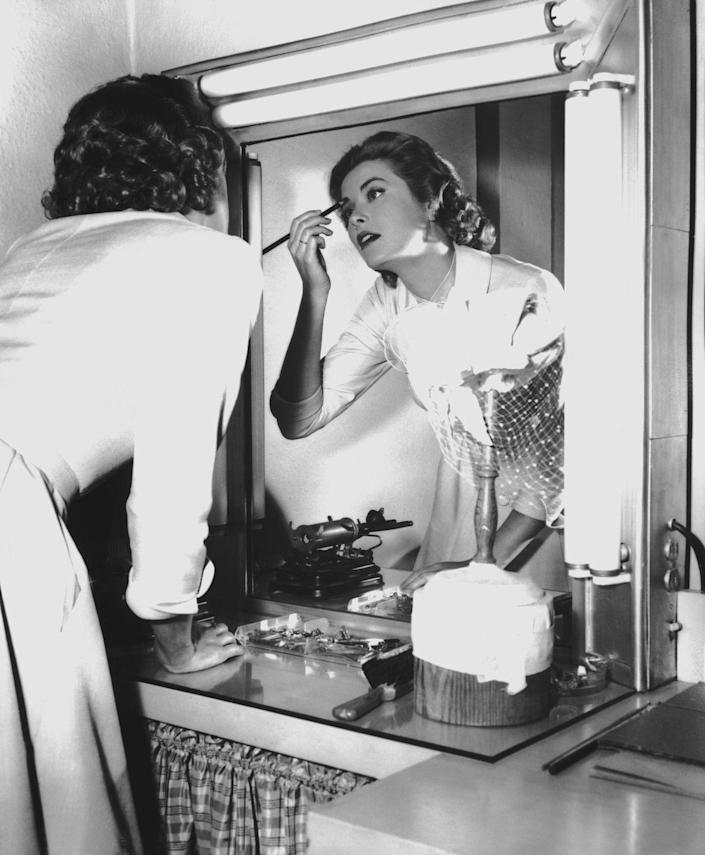 """<p>Kelly fixes her brows in her dressing room on set in 1954. The actress was known for her understated and polished beauty, and <a href=""""https://www.byrdie.com/grace-kelly-beauty-secrets"""" rel=""""nofollow noopener"""" target=""""_blank"""" data-ylk=""""slk:used two shades of blush"""" class=""""link rapid-noclick-resp"""">used two shades of blush</a> to achieve her signature high cheekbones. </p>"""