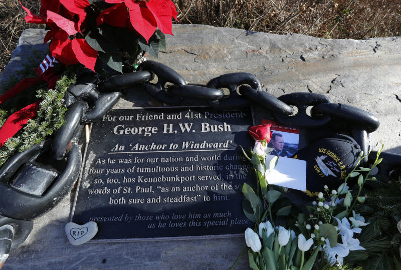 Flowers and mementoes lay near a plaque honoring former President George H. W. Bush at a makeshift memorial across from Walker's Point, the Bush's summer home, Saturday, Dec. 1, 2018, in Kennebunkport, Maine. Bush died at the age of 94 on Friday, about eight months after the death of his wife, Barbara Bush. (AP Photo/Robert F. Bukaty)