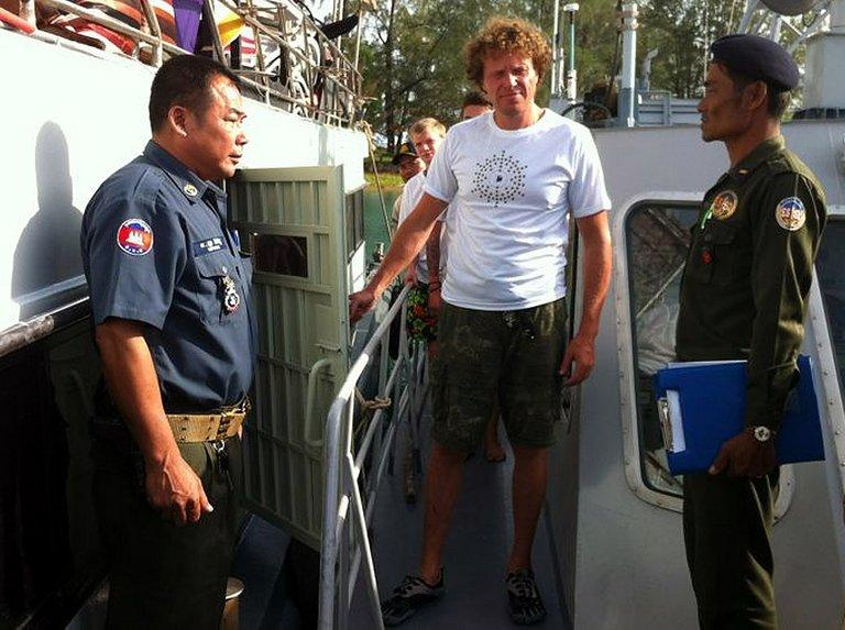 Cambodian military police escort Sergei Polonsky (centre) from a boat at Sihanoukville on December 30, 2012