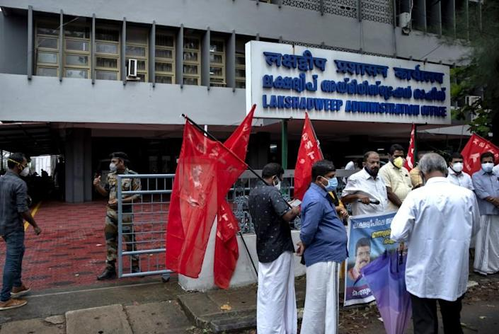 A security person checks on a visitor, left as activists of Centre of Indian Trade Unions (CITU) gather for a protest outside the Lakshadweep administration office in Kochi, Kerala state, India, Tuesday, June 15, 2021. A dozen activists of the CITU staged a peaceful protest here Tuesday expressing solidarity with the inhabitants of the archipelago who have been protesting against the reforms of a new administrator appointed by the Indian government. (AP Photo/R S Iyer)