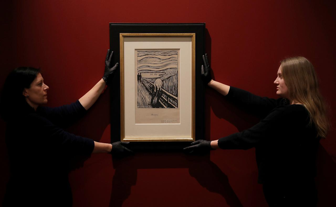 "Staff-members pose for a photograph as they hang a lithograph of  The Scream by Edvard Munch ahead of the exhibition ""Edvard Munch: love and angst"", soon to be on display at the British Museum in London, Britain, March 20, 2019. REUTERS/Peter Nicholls   NO RESALES. NO ARCHIVES"