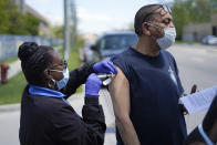 Registered nurse Precious McCormick administers a syringe of Moderna COVID-19 vaccine to Apolonio Mata in Detroit, Wednesday, May 12, 2021. In three weeks, more than 40 people have received vaccinations through the program to reach people who normally have little to no access to churches, community centers or other places where vaccines are being given. Mobile care teams consisting of two nurses and a peer support specialist accompany The Salvation Army's Bed & Bread trucks as they cruise Detroit, which lags far behind the state and nearby communities in percentage of people vaccinated. (AP Photo/Paul Sancya)