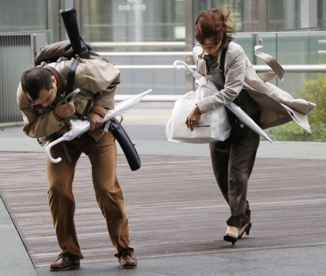 A couple struggle to walk in a strong wind caused by an approaching typhoon in Tokyo Monday, Sept. 16, 2013. Typhoon Man-yi was bearing down Japan, dumping torrential rains and flooding parts of the country's popular tourist destination of Kyoto, where 260,000 people were ordered to evacuate to shelters. The typhoon, one of the most powerful storms to lash Japan this season, was packing wind speeds of 162 kilometers (100 miles) per hour Monday morning and headed toward Tokyo. (AP Photo/Koji Sasahara)