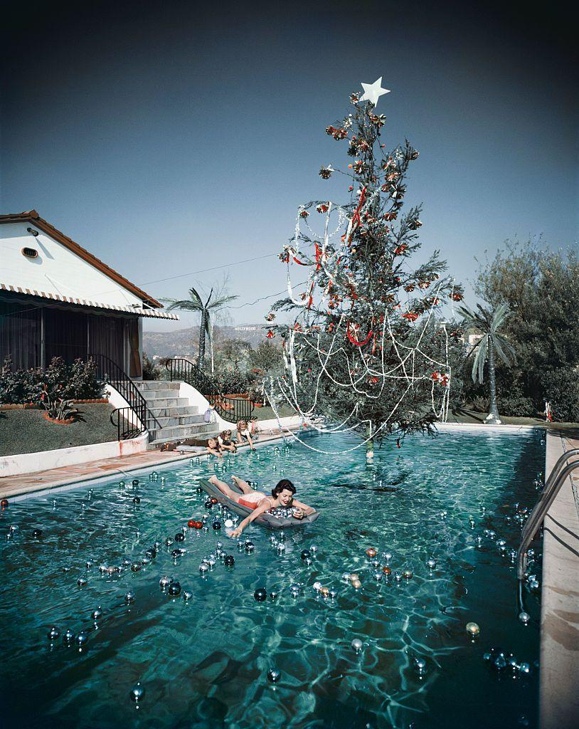 <p>The wife of Hollywood photographer Slim Aarons floats beneath a Christmas tree in their pool. Um, seriously, how amazing?</p>