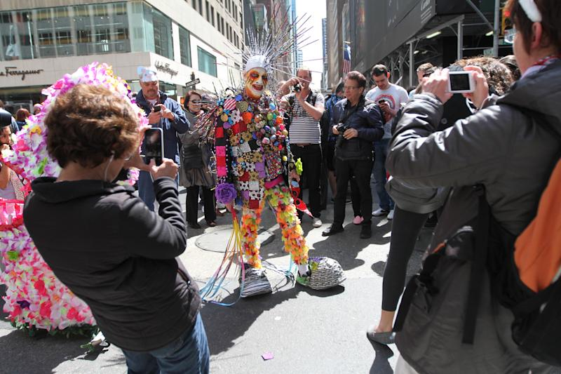 Dressed for the occasion, Rolando Vega, center, poses for photographs as he takes part in the Easter Parade along New York's Fifth Avenue, Sunday, April 20, 2014. (AP Photo/Tina Fineberg)