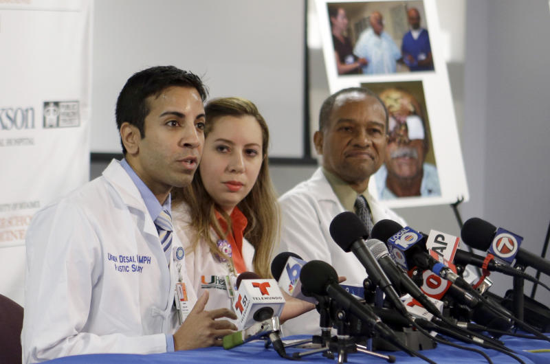 Doctor Urmen Desai, left, talks to reporters as Dr. Wrood M. Kassira, center, and Dr. Renaud Saint-Vil, right, look on during a news conference in Miami, Tuesday, May 21, 2013. The doctors gave an an update on the progress of Ronald Poppo, a homeless man whose face was mostly chewed off in a bizarre attack last year in Miami. The attack left Poppo blind, but the doctors say he's been working with an occupational therapist to learn how to take care of himself. The doctors say Poppo also has learned to play guitar and practices daily. (AP Photo/Alan Diaz)