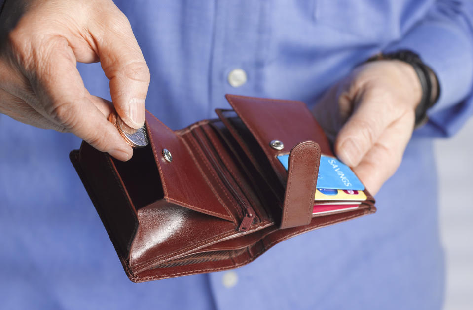 Close up of a man with a wallet putting coins inside