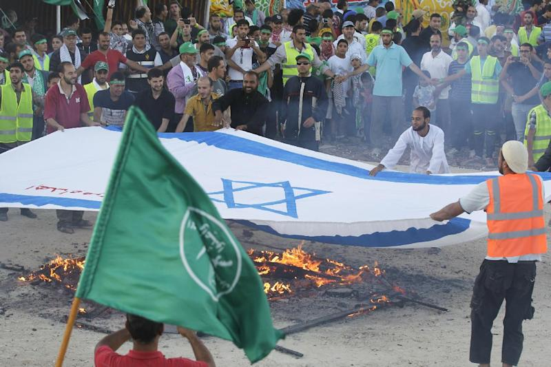 """Jordanian supporters of the Muslim Brotherhood set fire to a giant Israeli national flag during a protest to celebrate the """"Gaza victory"""" in the war against Israel, in the capital Amman on August 8, 2014 (AFP Photo/Khalil Mazraawi )"""