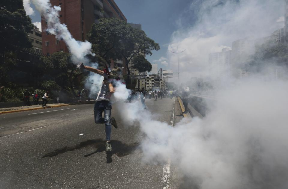 A demonstrator throws back a tear gas grenade launched by the Bolivarian National Police during a protest in Caracas, Venezuela, Saturday, April 8, 2017. Opponents of President Nicolas Maduro protest on the streets of Caracas on Saturday as part of a week-long protest movement that shows little sign of losing steam. (AP Photo/Fernando LLano)