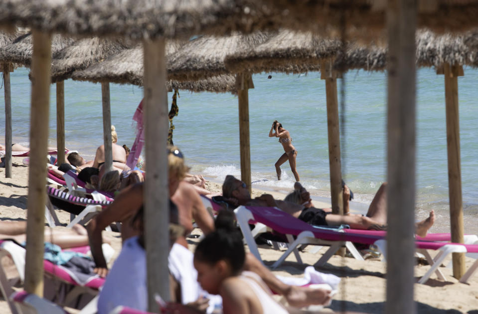 FILE - In this June 7, 2021, file photo, tourists sunbathe on the beach at the Spanish Balearic Island of Mallorca, Spain. Countries across Europe are scrambling to accelerate coronavirus vaccinations to outpace the spread of the delta variant in a high-stakes race to prevent hospital wards from filling up again with patients fighting for their lives. (AP Photo/Francisco Ubilla, File)