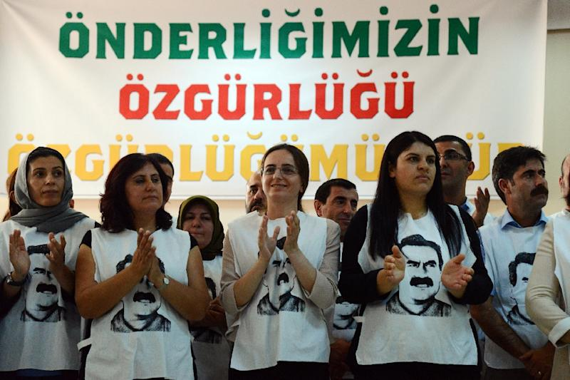 People wearing T-shirts featuring jailed PKK leader Abdullah Ocalan applaud during a speech by Turkey's pro-Kurdish People's Democratic Party co-chair Sebahat Tuncel speech on September 5, 2016 in Diyarbakir before starting a hunger strike (AFP Photo/Ilyas Akengin)