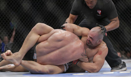 The referee stops the fight as Glover Teixeira, right, locks James Te Huna into a submission. (AP)