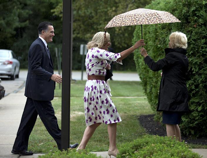 FILE - In this Sunday, Sept. 2, 2012 photo, Ann Romney, center, wife of Republican presidential candidate, former Massachusetts Gov. Mitt Romney, left, is handed an umbrella by Nancy Marriott as they arrive at the Church of Jesus Christ of Latter-day Saints for services on in Wofeboro, N.H. Former presidential candidate and Massachusetts governor Mitt Romney announced Monday, Dec. 3, 2012, he is getting a new job title: member of Marriott International's board of directors. (AP Photo/Evan Vucci)