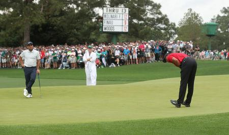 Golf - Masters - Augusta National Golf Club - Augusta, Georgia, U.S. - April 14, 2019. Tiger Woods of the U.S. reacts after missing a birdie putt as Francesco Molinari of Italy looks on on the 14th green during final round play. REUTERS/Jonathan Ernst