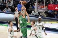 Milwaukee Bucks' Brook Lopez (11), Donte DiVincenzo (0) and Bobby Portis (9) defends as Dallas Mavericks center Kristaps Porzingis (6) goes up for a dunk in the second half of an NBA basketball game in Dallas, Thursday, April 8, 2021. (AP Photo/Tony Gutierrez)