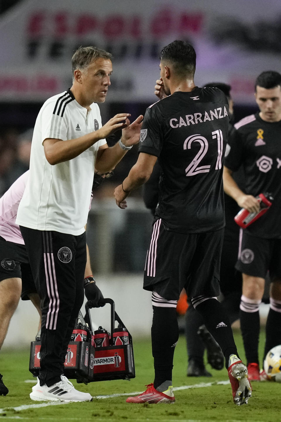 Inter Miami head coach Phil Neville talks to Inter Miami forward Julian Carranza on the sidelines during the second half of an MLS soccer match against Nashville, Wednesday, Sept. 22, 2021, in Fort Lauderdale, Fla. (AP Photo/Rebecca Blackwell)