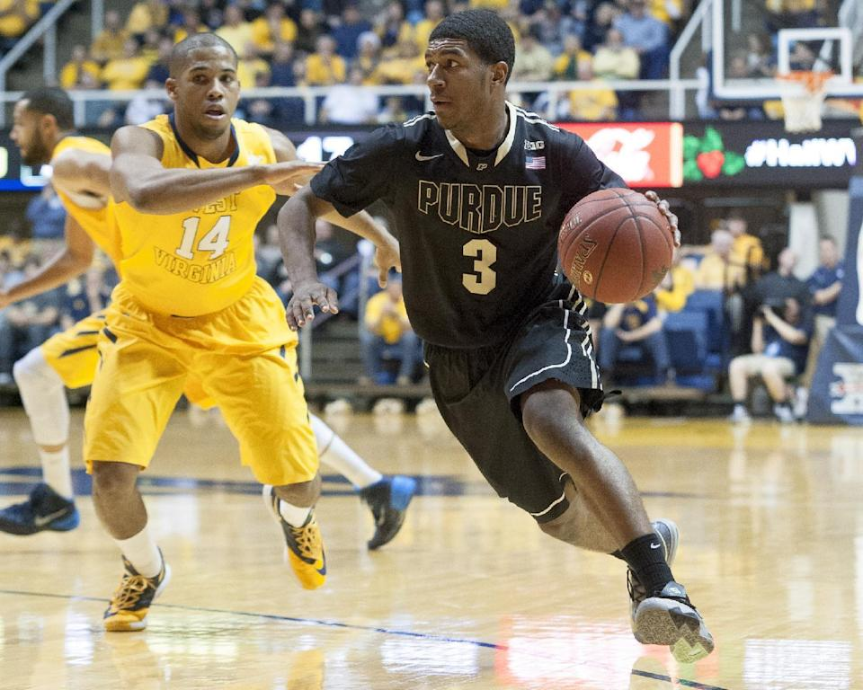 Purdue's Ronnie Johnson (3) drives by West Virginia's Gary Browne (14) during the first half of an NCAA college basketball game on Sunday, Dec. 22, 2013, in Morgantown, W.Va. (AP Photo/Andrew Ferguson)