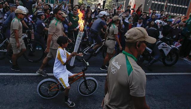 A resident of Sao Paulo carries the Olympic torch through the streets of Sao Paulo on July 24, 2016 (AFP Photo/Miguel Schincariol)