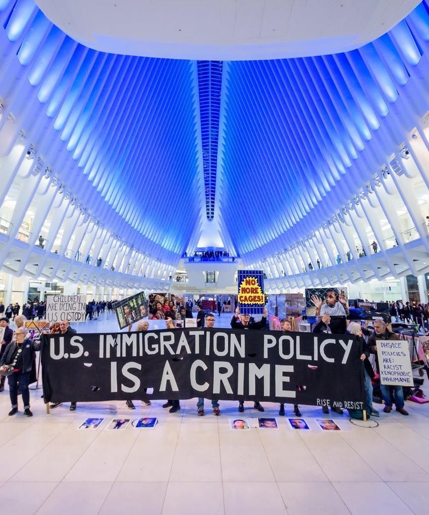 "MANHATTAN, NEW YORK, UNITED STATES – 2020/01/06: Protesters holding a banner at the silent protest. Members of the activist group Rise And Resist gathered a silent protest inside The Oculus at the World Trade Center, holding protest signs, a banner reading ""U.S. Immigration Policy Is A Crime"", photographs of the children who have died in ICE custody, and photographs of the detention camps to object to Border Patrol and ICE treatment of immigrants, refugees, and asylum seekers, calling on the Trump administration to immediately process all asylum seekers. (Photo by Erik McGregor/LightRocket via Getty Images)"