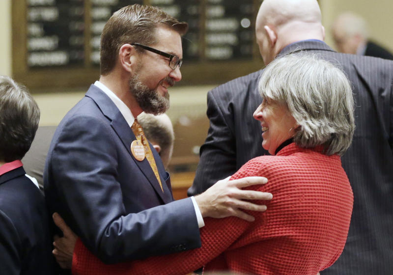 FILE - In this May 9, 2013 file photo, gay marriage sponsors Rep. Karen Clark, right, and Sen. Scott Dibble celebrate after the Minnesota House passed the gay marriage bill in St. Paul, Minn. The two openly gay  Minnesota state lawmakers, who respectively sponsored the measure in the state House and Senate, prepared to watch Democratic Gov. Mark Dayton sign the bill in a ceremony Tuesday, May 14, 2013, on the front steps of Minnesota's Capitol. (AP Photo/Jim Mone, File)