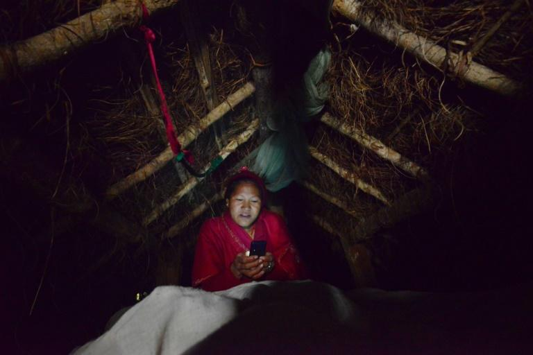 Nepalese woman Pabitra Giri checks her mobile phone inside a Chhaupadi hut during her menstruation period, in Surkhet District, some 520 km west of Kathmandu