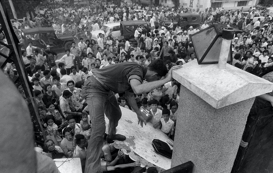 South Vietnamese civilians try to scale the wall of the U.S. embassy in Saigon