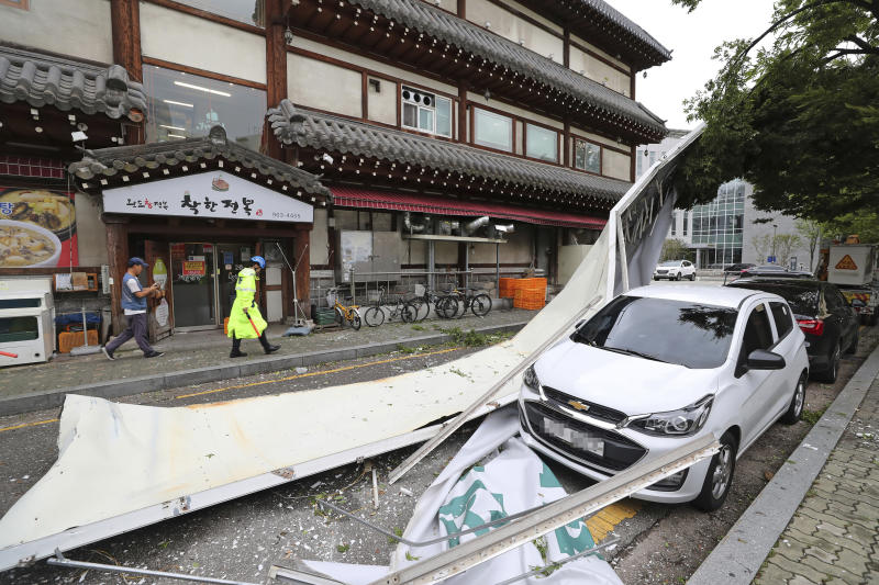 A vehicle is damaged by fallen signboard from a building as Typhoon Lingling brings strong wind and rain in Seoul, South Korea, Saturday, Sept. 7, 2019. The typhoon passed along South Korea's coast Saturday, toppling trees, grounding planes and causing at least two deaths before the storm system made landfall in North Korea. (Ryu Hyung-suck/Yonhap via AP)