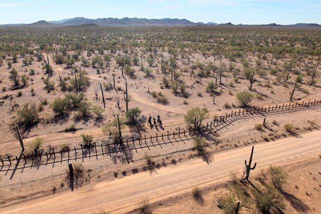 <p>A group of young men walk along the Mexican side of the U.S.-Mexico border fence in a remote area of the Sonoran Desert on Dec. 9, 2010, in the Tohono O'odham Reservation, Ariz. Federal agents flying over the group said the men would probably cross the fence after dark to make an illegal trek into the United States. (Photo: John Moore/Getty Images) </p>