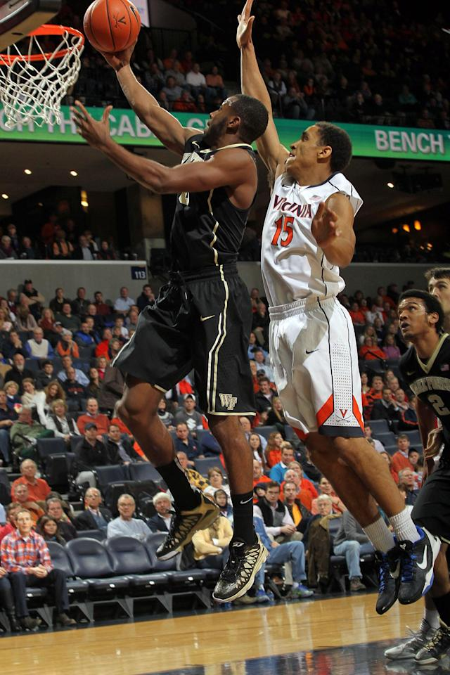Wake Forest guard Miles Overton (20) shoots in front of Virginia guard Malcolm Brogdon (15) during the first half of an NCAA college basketball game Wednesday, Jan. 8, 2014, in Charlottesville, Va. (AP Photo/Andrew Shurtleff)