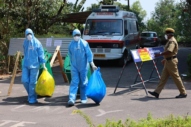 Heath officials in full protective apparel carry medical waste out of an isolation ward of Ernakulam medical in Kochi.