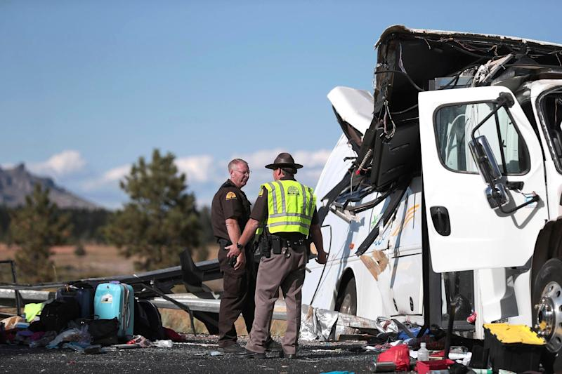 Highway patrolmen stand at the scene of the crash which killed at least four people in Utah on Friday: AP
