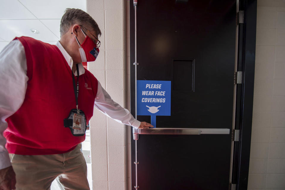 An usher places a sign near the fans' entrance to remind them to wear face coverings for a first-round game in the NCAA men's college basketball tournament, Saturday, March 20, 2021, at Assembly Hall in Bloomington, Ind. (AP Photo/Doug McSchooler)