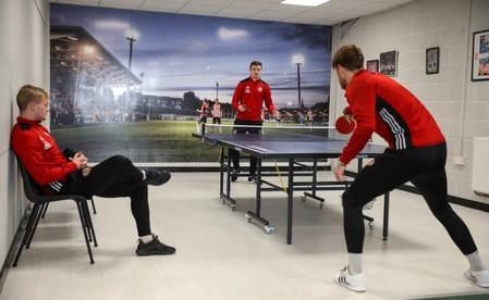 Derry City players play table tennis at the club's gym facility in Londonderry, Northern Ireland