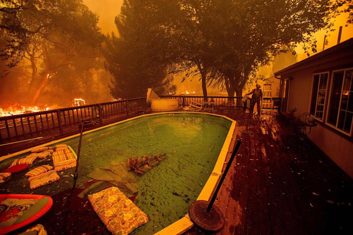 A firefighter gathers water from a pool while battling the Ranch Fire near Clearlake Oaks, Calif., on Aug. 4. (Photo: Noah Berger/AFP/Getty Images)