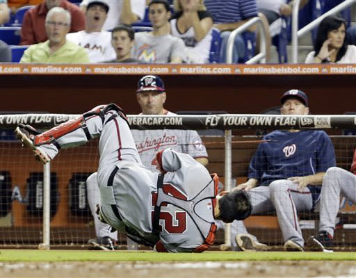 Washington Nationals catcher Kurt Suzuki attempts to catch a ball hit by Miami Marlins' Donovan Solano during the sixth inning of a baseball game, Monday, April 15, 2013 in Miami. The Nationals defeated the Marlins 10-3. (AP Photo/Wilfredo Lee)