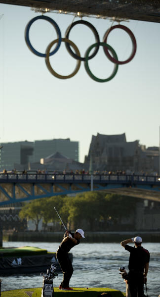 Spanish golfer Sergio Garcia, left, hits a shot as he and U.S. golfer Dustin Johnson, right, take it in turns to hit golf balls at a floating golf hole on the River Thame as Olympic rings hang from Tower Bridge ahead of the 2012 Summer Olympics, Monday, July 23, 2012, in London. The two golfers took part in the stunt to promote a range of footwear for Adidas who they are both sponsored by. Golf is set to be included as an Olympic sport in the next games in 2016. (AP Photo/Matt Dunham)