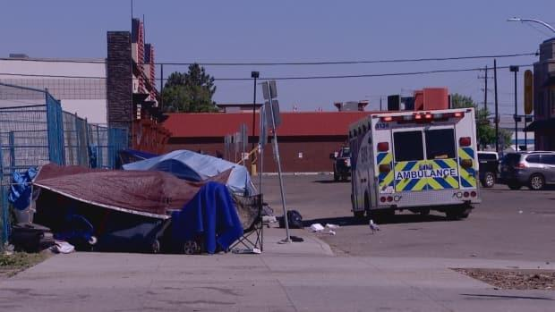 EMS workers deal with a patient near the Hope Mission, where close to 20 tents are set up, and vulnerable people hide out in shade to stay cool. (Jamie McCannel/CBC - image credit)